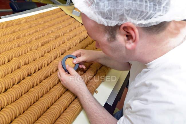 Человек контролирует качество печенья с помощью трафарета на хлебопекарной фабрике — стоковое фото