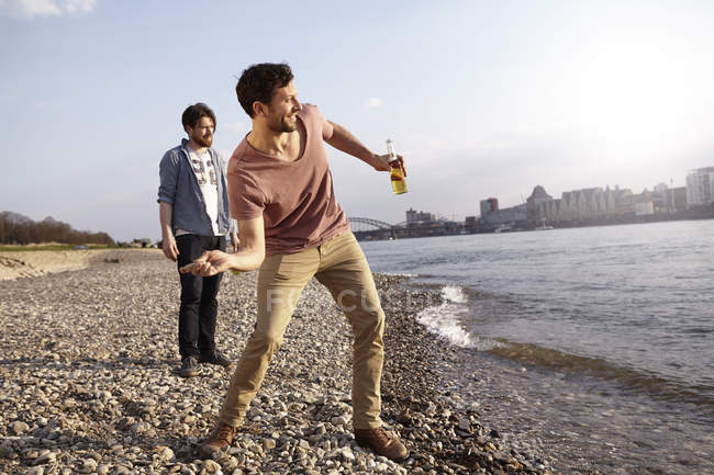 Two friends skipping stones at river — Stock Photo