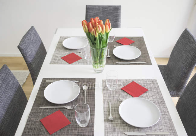 Laid table for four persons with flower vase of tulips — Stock Photo