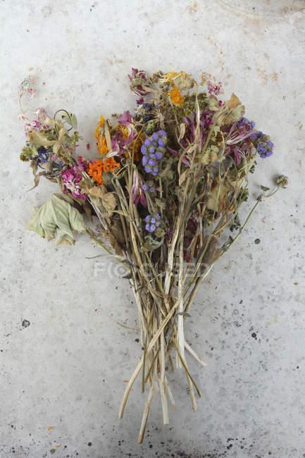 Manojo de ámbito marchitadas flores y rosas en superficie gris - foto de stock