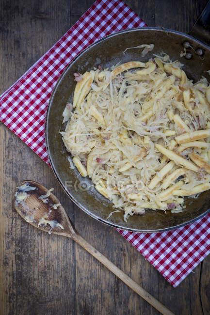 Деревянной ложкой и Сковорода палец образный картофельные кнедлики с капустой и беконом на ткани — стоковое фото