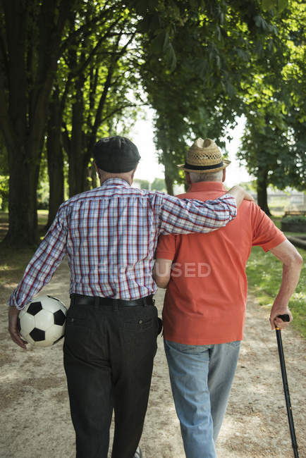 Rear view of two old friends walking in the park with football — Stock Photo