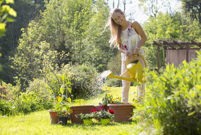 Smiling teenage girl watering potted plants in the garden — Stock Photo