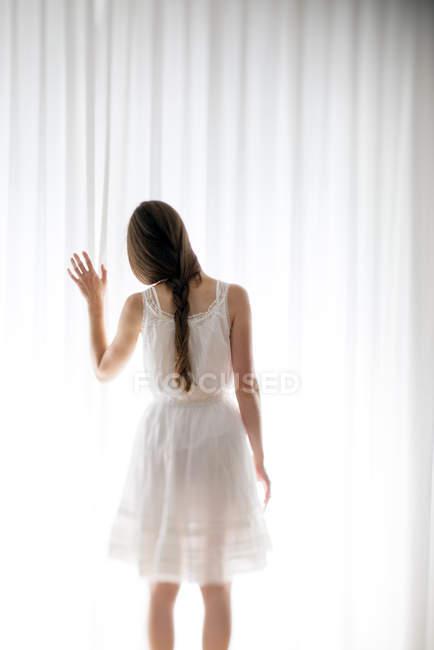 Молодая женщина трогательно белый занавес, вид сзади — стоковое фото