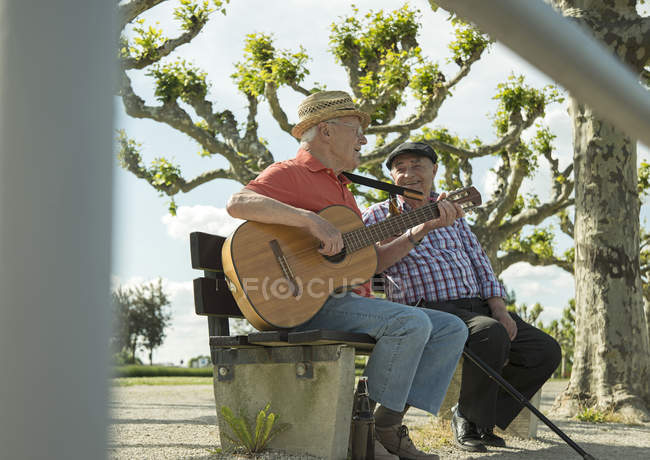 Two old friends with guitar sitting on bench at park — Stock Photo