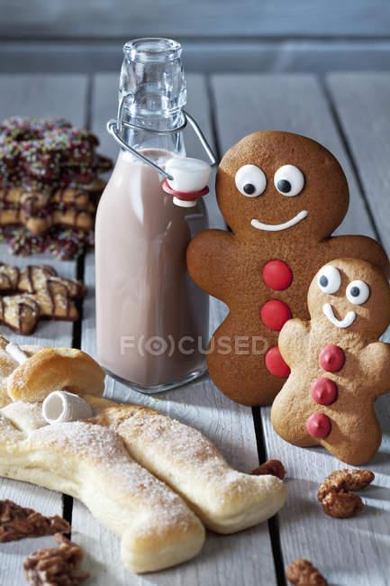 Dos hombres de pan de jengibre, botella de cacao, galletas Stutenkerl y Navidad en madera gris - foto de stock