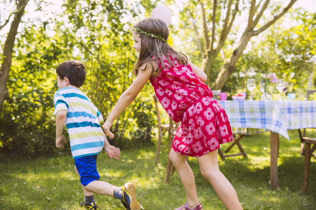Garçon et fille jeu tag dans le jardin — Photo de stock