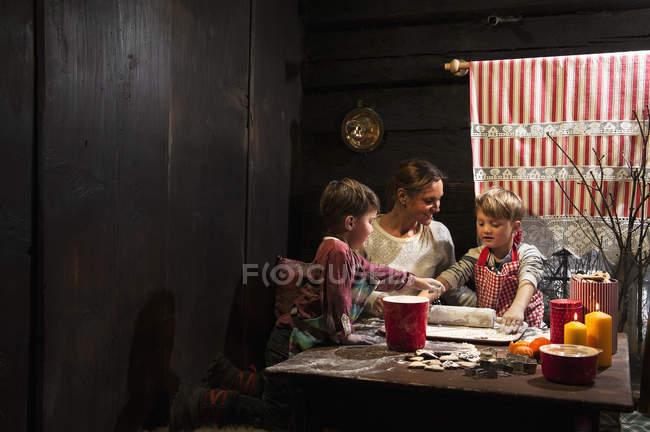 Mutter mit ihren zwei kleinen Söhnen Backen Weihnachtsplätzchen zur Adventszeit — Stockfoto