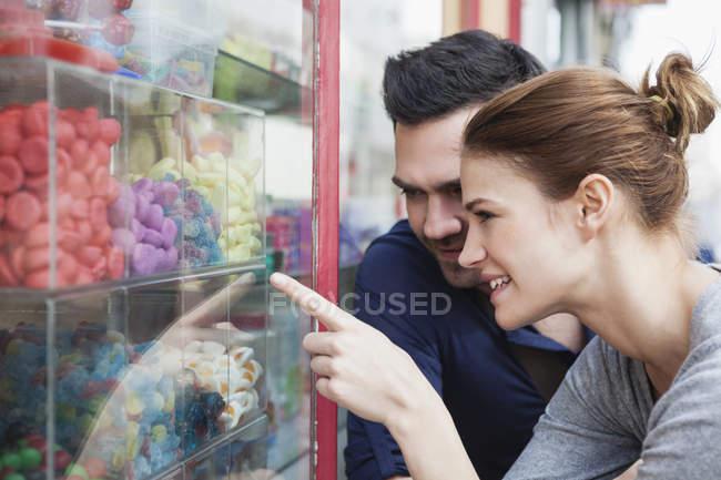 Paar betrachtet Süßigkeiten im Schaufenster — Stockfoto