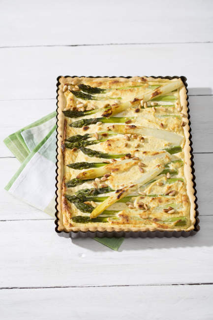Asparagus tart and kitchen towel on white wood — Stock Photo