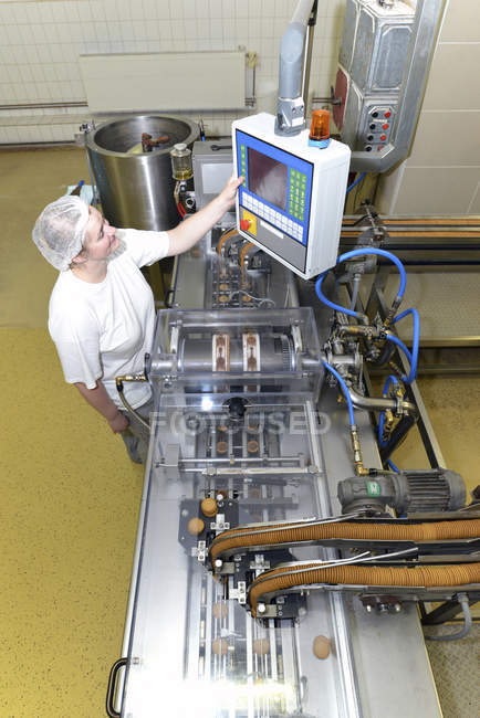 Woman operating control of machine in a baking factory, elevated view — Stock Photo