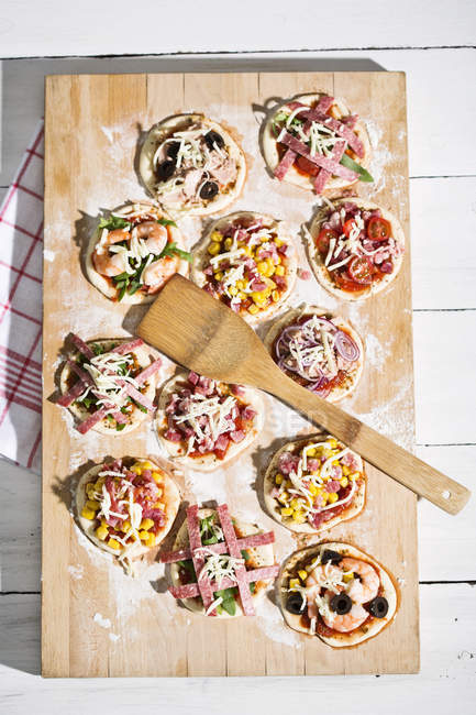 Home made mini pizzas on chopping board — Stock Photo