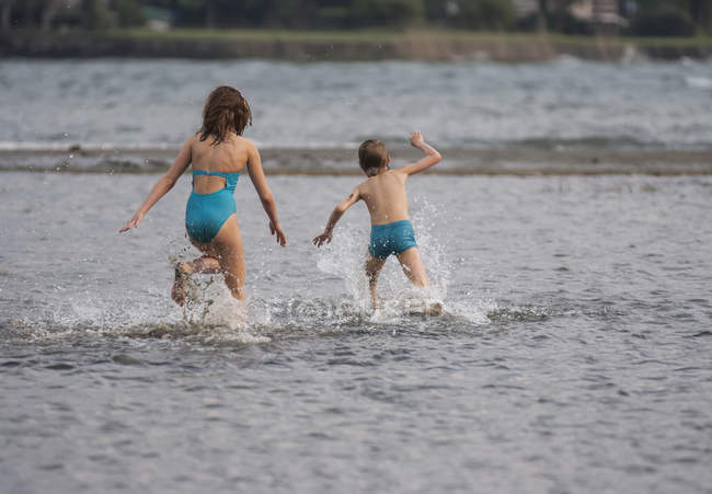 Heureux jouer les enfants dans le lac dans la nature — Photo de stock