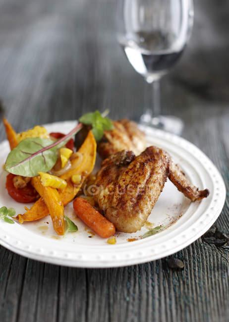Placa de pollo asado, tomates cherry, zanahoria, rodajas de batata y maíz sobre madera gris - foto de stock