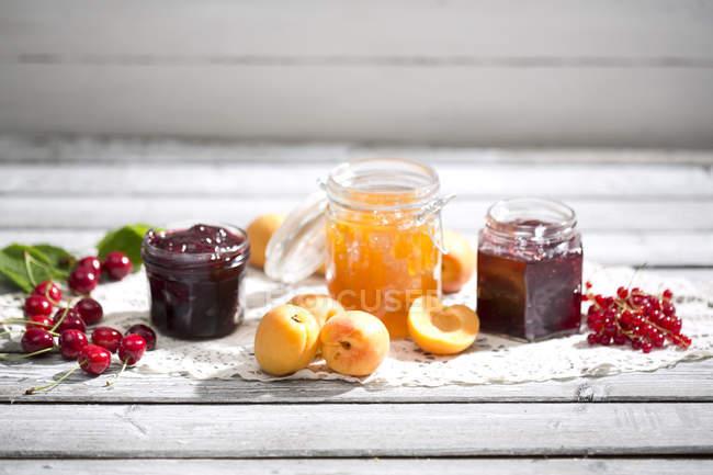 Вишневого варенья и вишни, абрикосового джема и абрикосы, варенье из смородины и красная смородина на Долли — стоковое фото