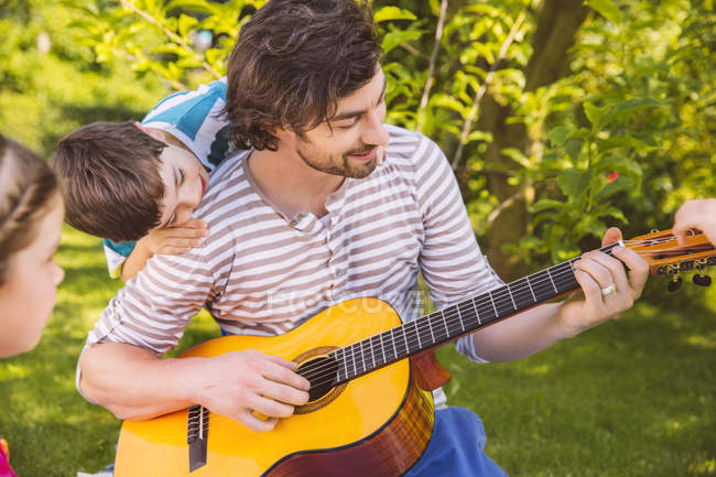 Father with children playing guitar in garden — Stock Photo