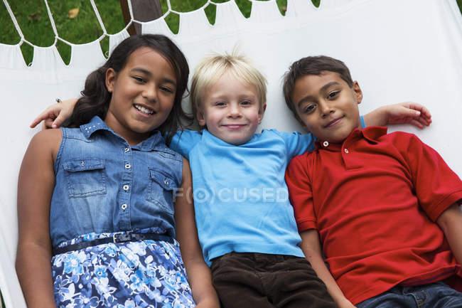 Three happy children lying in hammock — Stock Photo