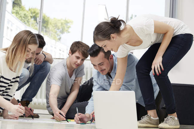 Group of creative professionals drawing sketches on floor with laptop — Stock Photo