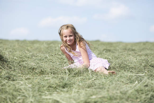 Cute young sitting on meadow with hay — Stock Photo