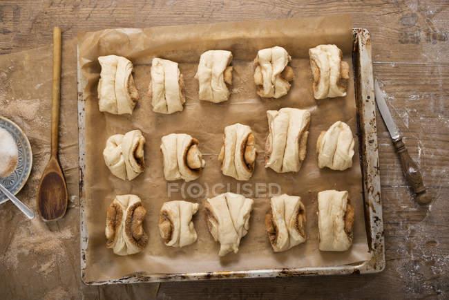 Franzbroetchen cruda en una bandeja para hornear, ve desde arriba - foto de stock