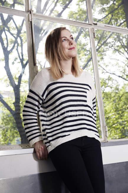 Жінка біля вікна мислення — стокове фото