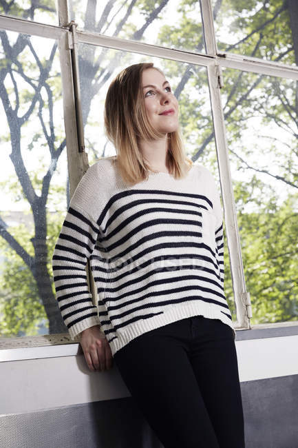 Frau am Fenster denkt nach — Stockfoto