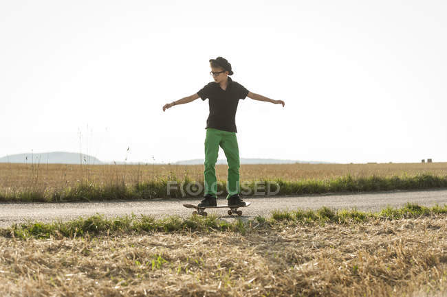 Boys standing on his skateboard in front of a stubble field — Stock Photo