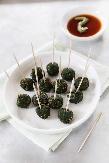 Assiette de brochettes de boules de sésame aux épinards et bol à tremper de sauce — Photo de stock