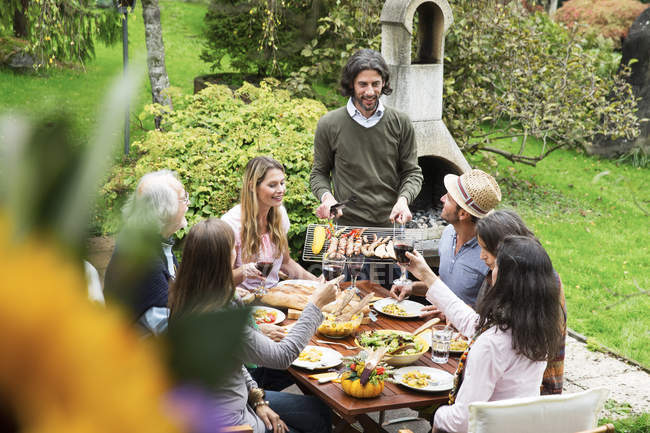 People sitting at table outdoor on a barbecue — Stock Photo