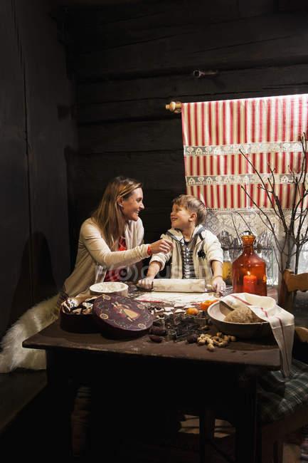Mutter und ihr kleiner Sohn Backen Weihnachtsplätzchen zur Adventszeit — Stockfoto