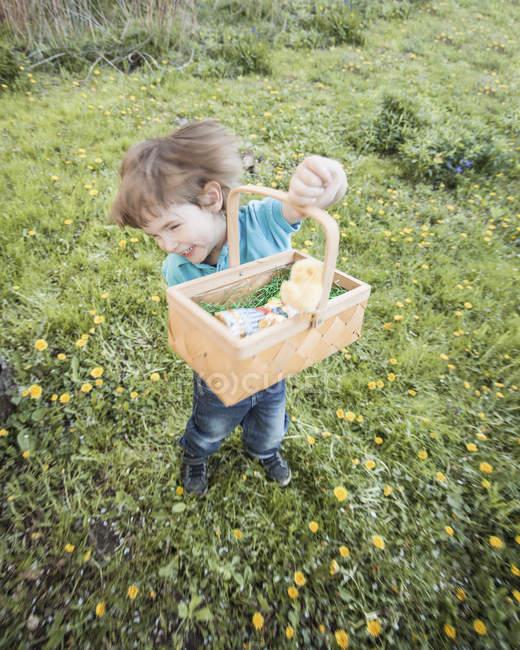 Счастливый маленький мальчик с корзинкой танцует в саду — стоковое фото