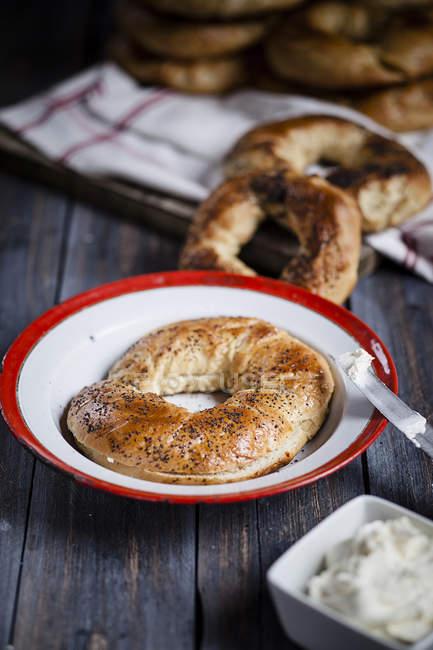 Плита бублик, домашней выпечки и чаша плавленого сыра — стоковое фото