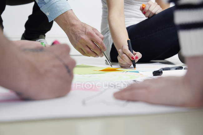 Professionnels de la création de dessin sur papier sur le plancher — Photo de stock