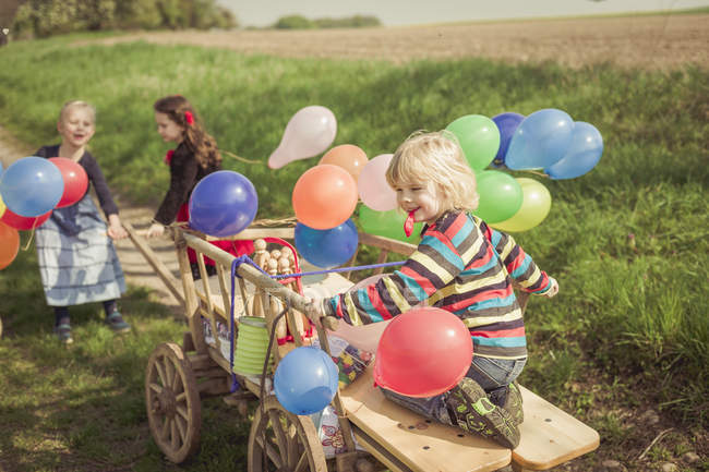Three children playing with wooden trolley and balloons — Stock Photo