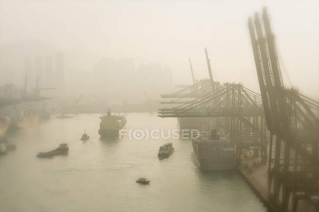 Container harbour with cranes and ships in morning mist, Hong Kong, China — Stock Photo