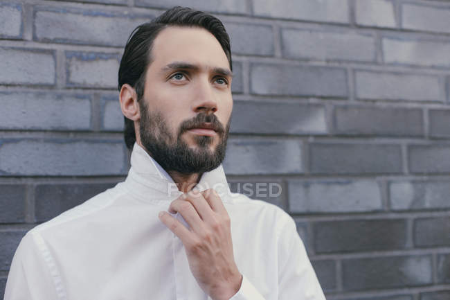 Portrait of young man folding up the collar of his shirt — Stock Photo