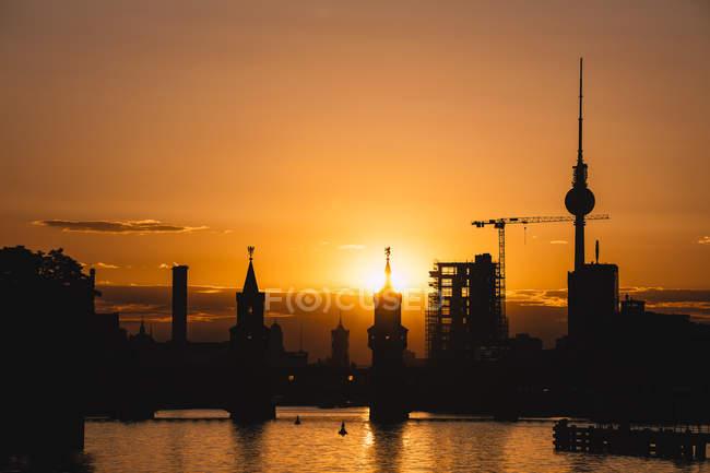 Allemagne, Berlin, Friedrichshain-Kreuzberg, pont Oberbaum et rivière Spree, tour de télévision de Berlin en arrière-plan au coucher du soleil — Photo de stock