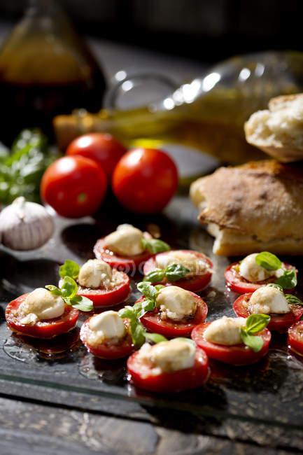 Ломтики сыра моцарелла сыр, помидоры и Василия травы — стоковое фото