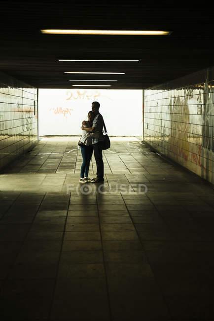 Pareja joven abrazándose en un oscuro paso subterráneo - foto de stock