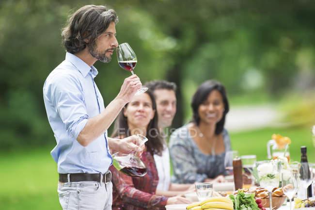 Mann, die Verkostung Rotwein auf einer Gartenparty — Stockfoto