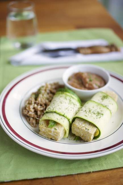 Tempeh wrapped in zucchini, with a rhubarb mustard sauce and spelt on plate — Stock Photo