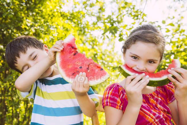 Діти, які їдять скибочками кавуна в саду — стокове фото