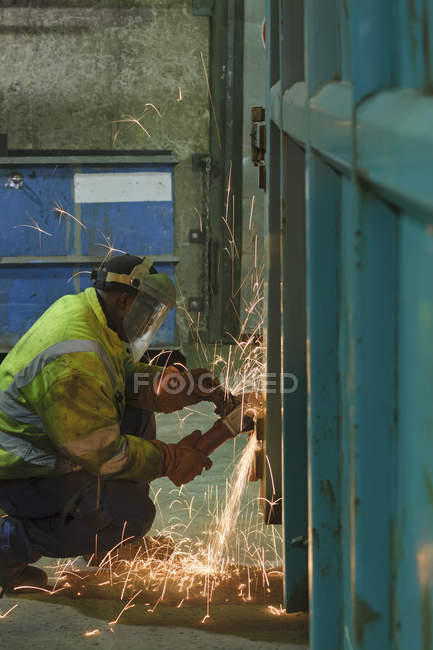Man working at container in a scrap metal recycling plant — Stock Photo
