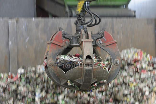 Грейферный захват алюминиевых банок в завод по переработке металлолома — стоковое фото