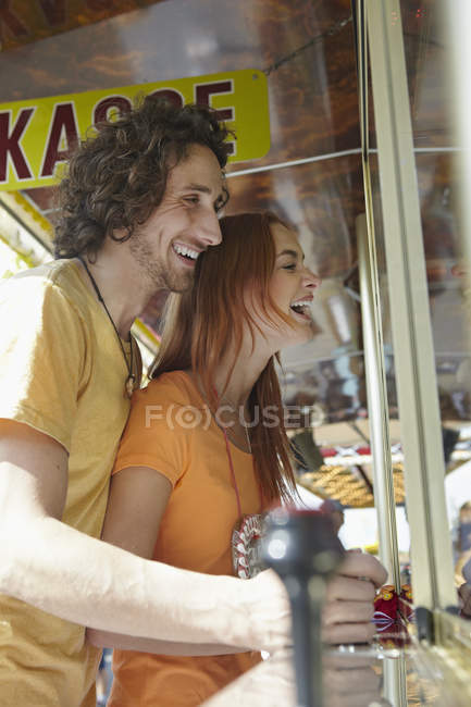 Happy young couple on a funfair by the ticket window — Stock Photo