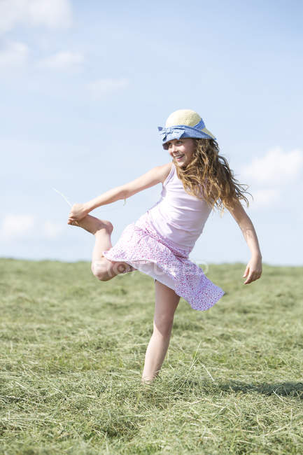 Cute young girl on meadow with hay — Stock Photo