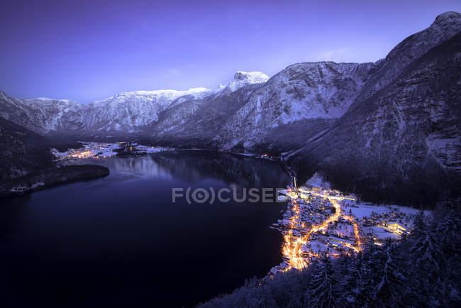 Vista de noche de Hallstatt y el lago con las montañas Dachstein en Salzkammergut, Austria - foto de stock