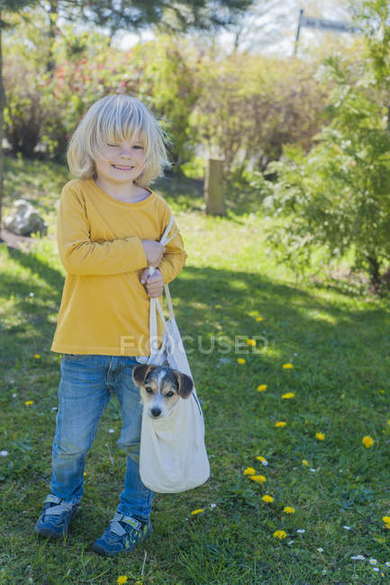Boy carrying Jack Russel Terrier puppy in bag — Stock Photo