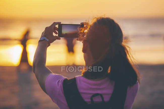 Woman on the beach photographing sunset with her smartphone — Stock Photo
