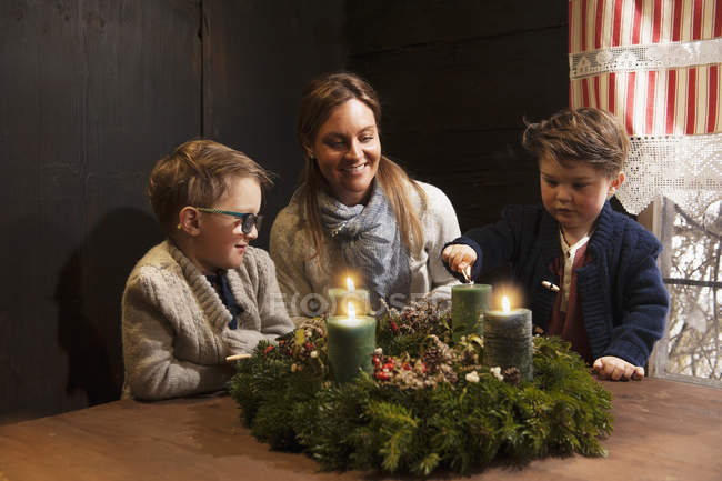 Mother and her two little sons lightning candles on a Advent wreath — Stock Photo